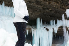 Closeup of female hands holding pregnant belly on winter background. Stock Photo