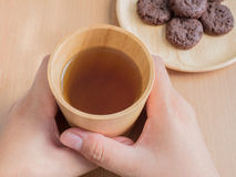 Closeup of female hands holding wood cup of Organic Jasmine Tea with cookies Royalty Free Stock Photography