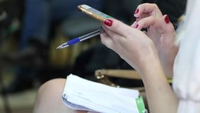 Closeup of a female hands holds a pen and typing text message on smartphone sitting. In a conference room stock footage