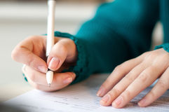Closeup of female hands signing document in blue sweater with black pen. Closeup of female hands signing document in blue sweater. black handle royalty free stock image