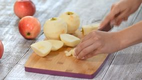 Closeup of female hands slicing apple with knife on wooden cutting board in domestic kitchen. Closeup of female hands slicing apple with knife on wooden cutting stock footage