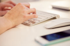 Closeup of a female hands typing on laptop keyboard in the office Royalty Free Stock Photo