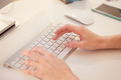 Closeup of a female hands typing on laptop keyboard in the office Royalty Free Stock Photos