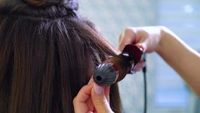 Closeup female hands using curling iron making curls on long dark hair. People, cosmetics, care, lifestyle, style concept stock footage
