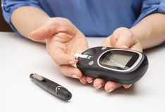 Closeup female hands using glucometer scanner Stock Photo