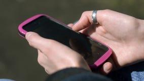 Closeup of female hands using smartphone browsing social media. Closeup of female hands using smartphone browsing social media sitting in the park stock video