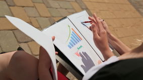 Closeup of female hands working with documents, charts outdoors. stock video footage