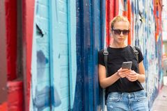 Woman using smartphone against colorful graffiti wall in New York city, USA. royalty free stock photos