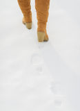 Closeup on female legs in boots walking on snow Royalty Free Stock Image