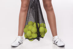 Closeup of Female Legs Holding Tennis Balls In Mesh in Studio En Royalty Free Stock Image