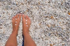 Closeup of female legs with pebbles on white sandy Royalty Free Stock Images