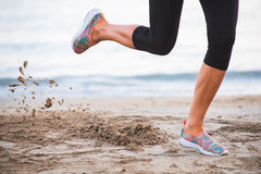 Closeup of female legs running on beach at sunrise in morning with sand in-motion Stock Photography