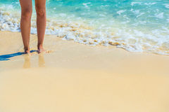 Closeup of female legs on tropical beach. Women's legs on the sa Stock Images