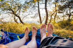 Closeup of female and male feet lying on blanket at sunset. Romance in forest meadow Stock Photos