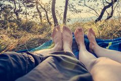 Closeup of female and male feet lying on blanket at sunset. Romance in forest meadow Stock Photo