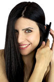 Closeup of female model brushing her long hair Royalty Free Stock Images