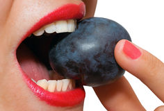 Closeup of female mouth biting a plum Stock Photo