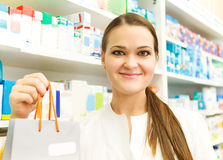 Closeup of a female pharmacist holding packet at drugstore Stock Image