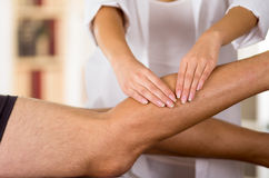 Closeup female physio therapist hands working on male patients legs, blurry clinic background Stock Images