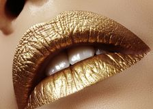 Closeup Female Plump Lips with Gold Color Makeup. Fashion Celebrate Make-up, Glitter Cosmetic. Christmas Style. Beautiful closeup with female plump lips with royalty free stock photo