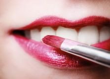 Closeup female red pink lips with makeup lipstick brush Stock Photos