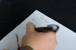 Closeup of female right hand writing on paper Royalty Free Stock Images