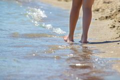 Closeup of a female`s bare feet walking at a beach at the morning. Concept of the travel,vacation. Stock Photos