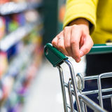 Closeup of female shopper with trolley Royalty Free Stock Photos