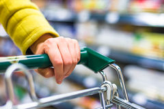 Closeup of female shopper with trolley Royalty Free Stock Images