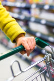 Closeup of female shopper with trolley at supermarket Stock Photo