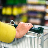 Closeup of female shopper with trolley at supermarket Stock Photography