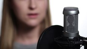 Closeup female singer recording track in studio stock footage