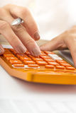 Closeup of female student hand calculating using orange desk cal Royalty Free Stock Photo