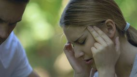 Closeup of female suffering from migraine, man calling ambulance, support. Stock footage stock footage
