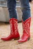 Female in red cowboy boots on gravel road. Closeup of female wearing jeans in red cowboy boots standing on a gravel road royalty free stock images