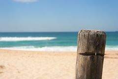 Closeup of fence post at surfing beach on sunny summers day. With wave breaking in the background Stock Photography