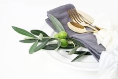 Closeup of festive table summer setting with golden cutlery, olive branch, grey linen napkin, porcelain dinner plate and. Silk ribbon on white table background royalty free stock image