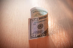 Closeup of fifty dollar bills on wooden table Stock Image