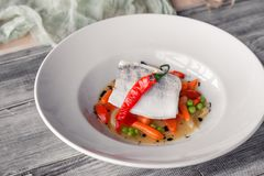 Closeup fillet stewed pike perch with vegetables, chilli pepper, tomato, onion, mini carrot with sauce served on table in royalty free stock photo