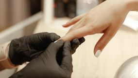 Closeup of finger massage. Manicurist in black gloves massages fingers of a female client after a manicure procedure in a beauty salon. Closeup of finger massage stock video footage