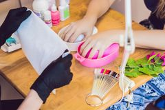 Closeup finger nail care by manicure specialist in beauty salon. Royalty Free Stock Photo