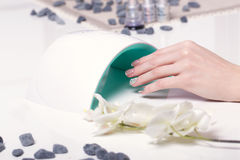 Closeup finger nail care by manicure specialist in beauty salon. Manicurist clear cuticle professional electric Dryer for manicure and pedicure Royalty Free Stock Images