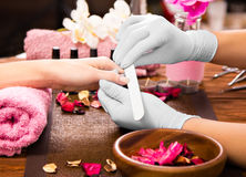Closeup finger nail care by manicure specialist in beauty salon. Royalty Free Stock Photography