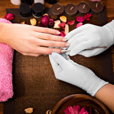 Closeup finger nail care by manicure specialist in beauty salon. Stock Image