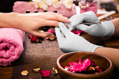 Closeup finger nail care by manicure specialist in beauty salon. Manicurist clear cuticle professional tool for manicure and pedicure Royalty Free Stock Image