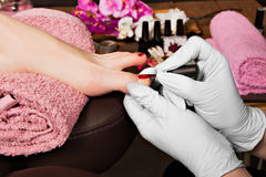 Closeup finger nail care by pedicure specialist in beauty salon. Stock Images