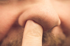 Closeup finger nose. Closeup of a finger in the nose Stock Photography