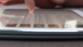 Closeup Finger Touching Tablet Computer Touchscreen. Video is defocused. No trademarks, no other details stock footage