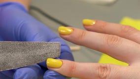 Closeup of fingernail shape correction using nail file. Yellow polish. Last manicure strokes. Beauty salon. Blue glowes stock video