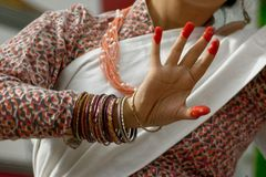 Painted fingers of a moving nepalese dancer. Closeup on fingers and bracelets of a nepalese dancer during her performance royalty free stock images